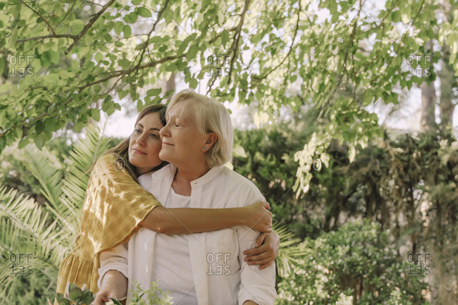 Loving daughter embracing mother while standing against plants in yard