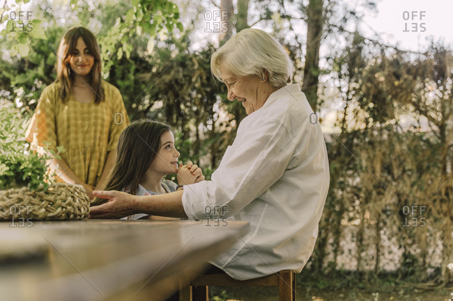 Woman looking at senior woman playing with cute granddaughter in yard