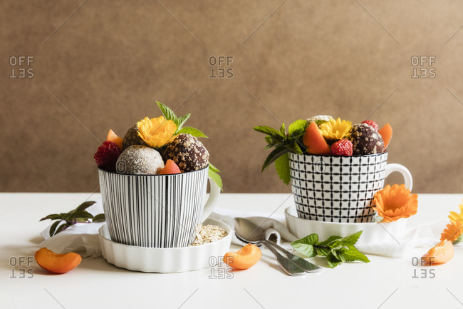 Dessert with energy balls (raw confectionery) and fresh fruits and flowers