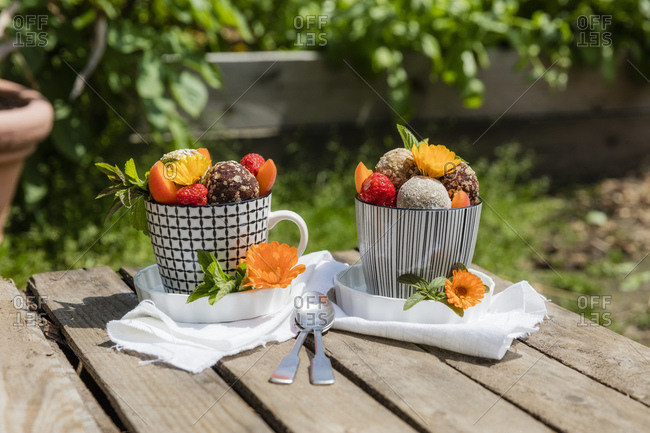 Dessert with energy balls (raw confectionery) and fresh fruits and flowers on garden table
