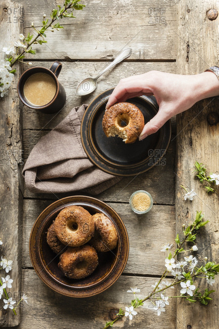 Hand reaching for homemade donut with sugar and cinnamon