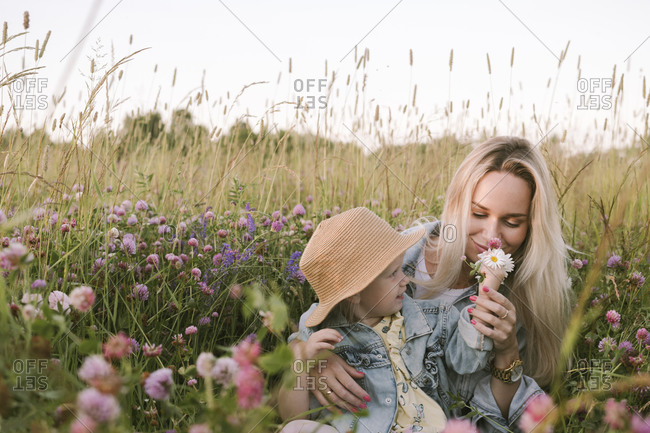 Mother with her daughter smelling on flowers in field
