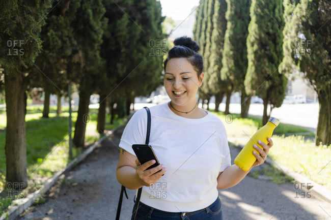 Smiling curvy young woman with mobile phone and bottle in a public park