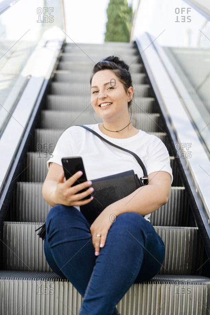 Portrait of a smiling curvy young woman sitting on escalator with mobile phone