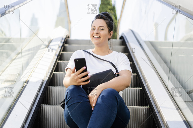 Portrait of a happy curvy young woman sitting on escalator with mobile phone