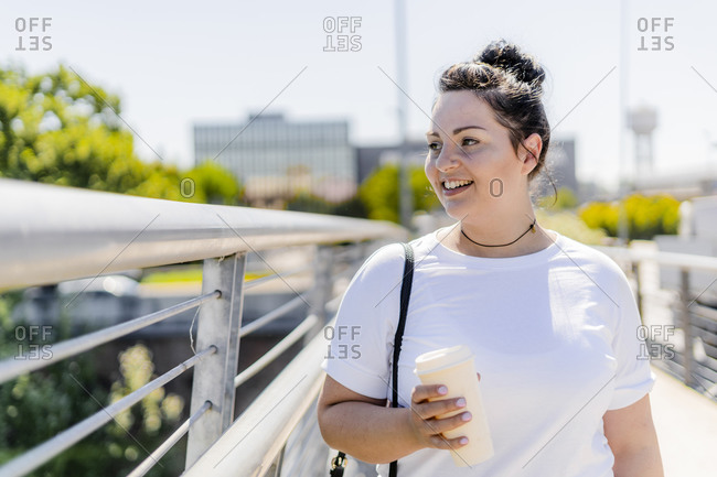 Smiling curvy young woman with takeaway drink in the city