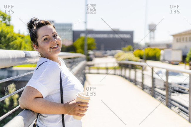 Portrait of a smiling curvy young woman with takeaway drink in the city