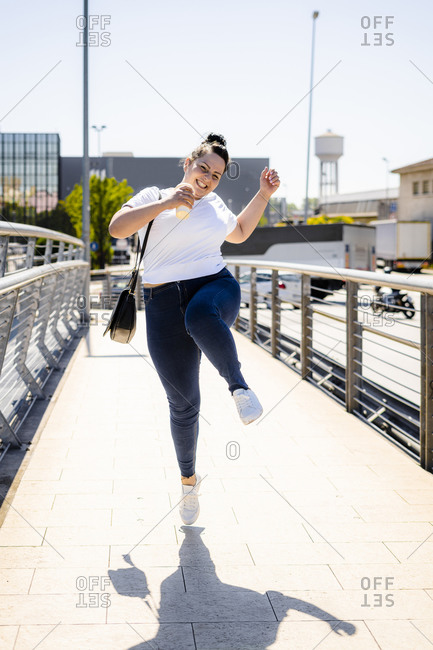 Carefree curvy young woman jumping in the city
