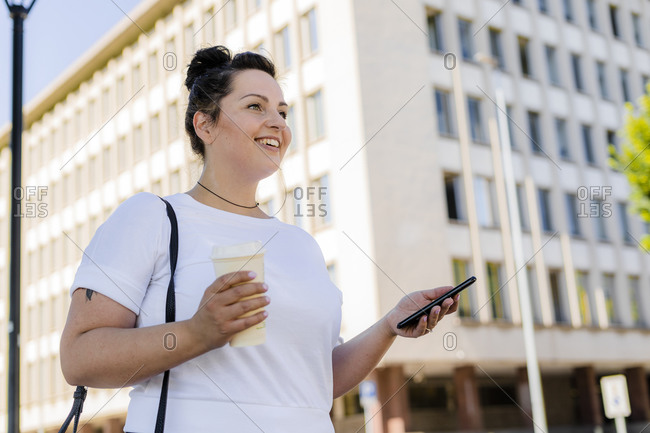 Smiling curvy young woman holding mobile phone in the city