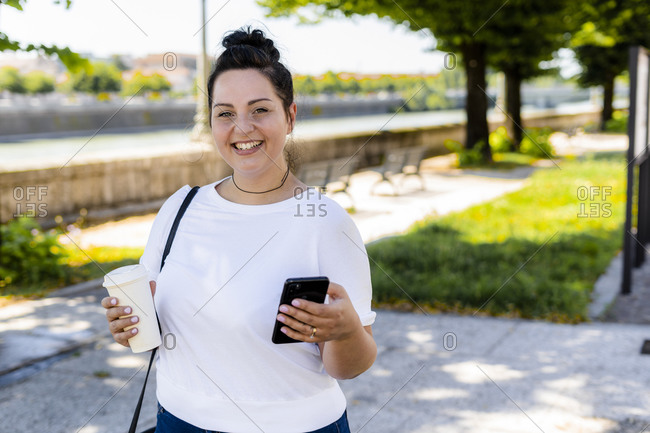Portrait of a smiling curvy young woman with takeaway drink and mobile phone in the city