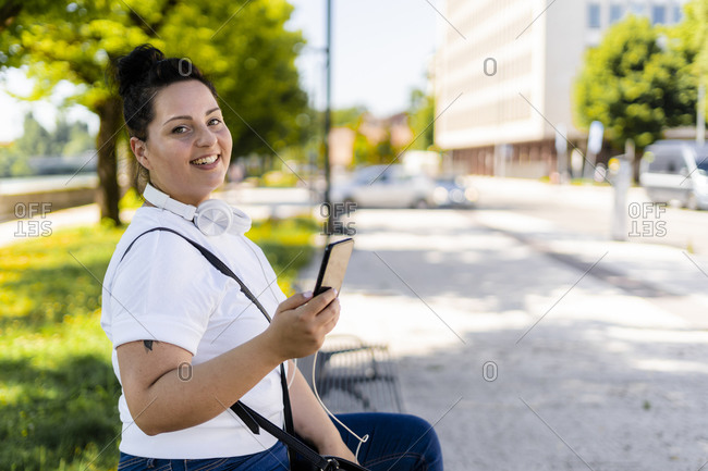 Portrait of a smiling curvy young woman with mobile phone sitting on a bench in the city