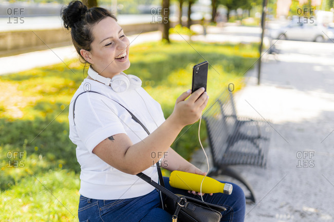 Happy curvy young woman using mobile phone in the city