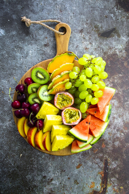 Fruit salad with watermelon- kiwi- passion fruit- grape- cherry- peach and melon on chopping board