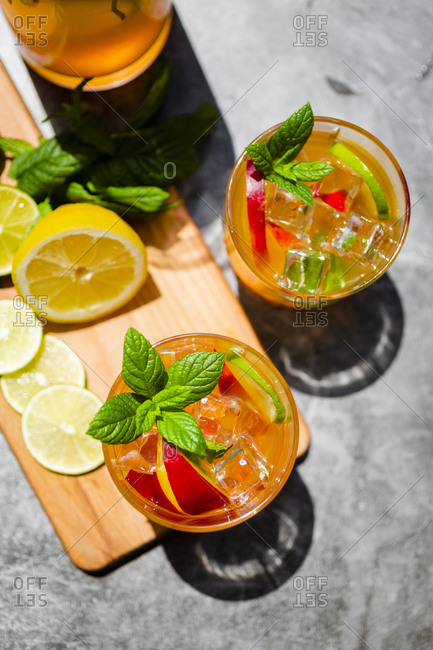 Cocktail with peach- mint and lime and ice cubes