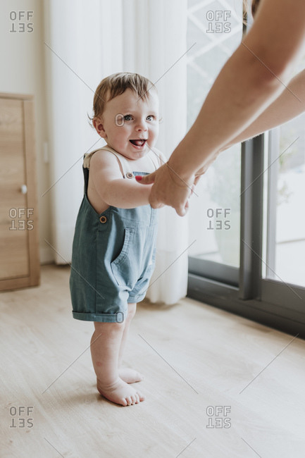 Baby girl holding mother's hands while learning to walk on floor at home