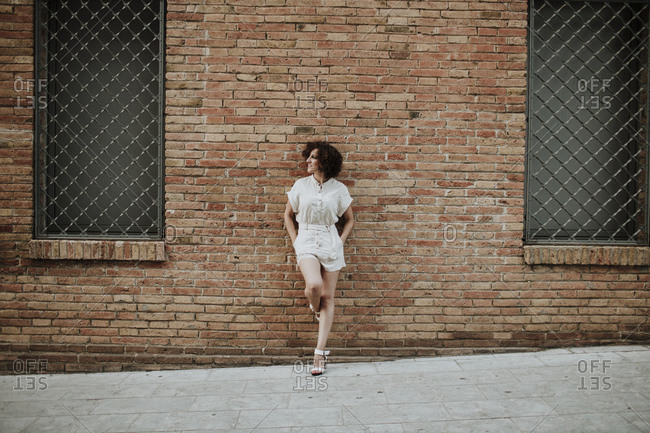 Mid adult woman with curly hair leaning on brick wall in city