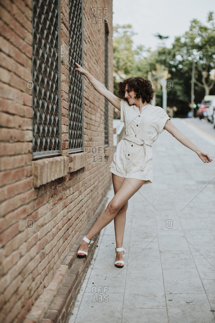 Mid adult woman with arms outstretched standing on street by brick wall in city