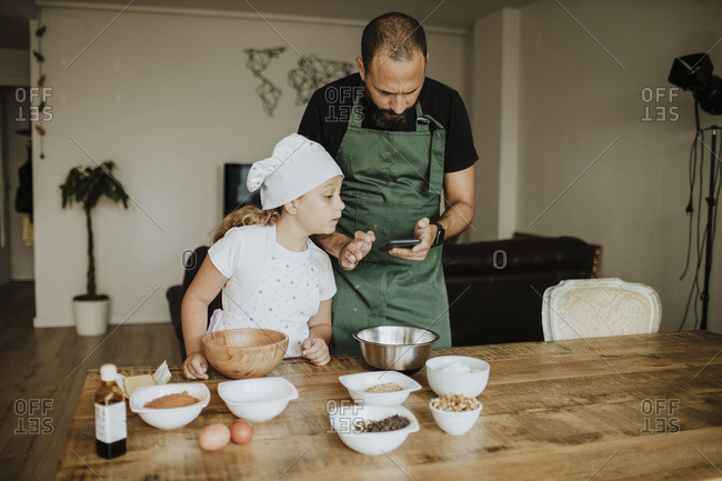 Father and daughter baking cookies and using smartphone at home