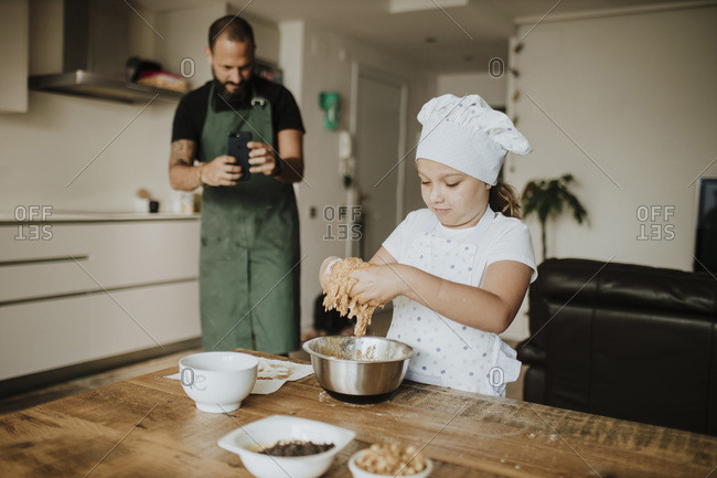 Father and daughter baking cookies at home- father taking a picture with smartphone
