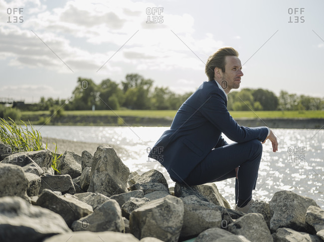 Thoughtful male entrepreneur sitting on rock at riverbank against sky