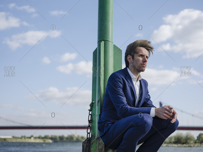 Thoughtful businessman with hands clasped crouching by pole against sky