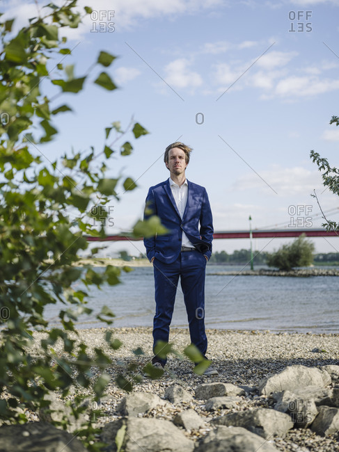 Serious Businessman standing against Rhine river and sky