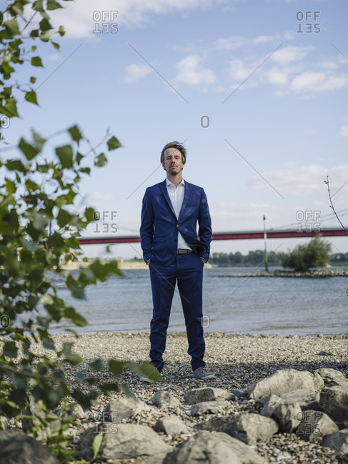 Businessman with eyes closed standing against Rhine river and sky