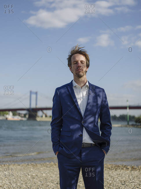 Male entrepreneur with eyes closed standing against Rhine river