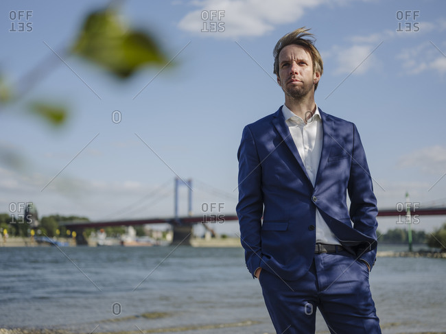 Thoughtful male professional looking away while standing against Rhine river