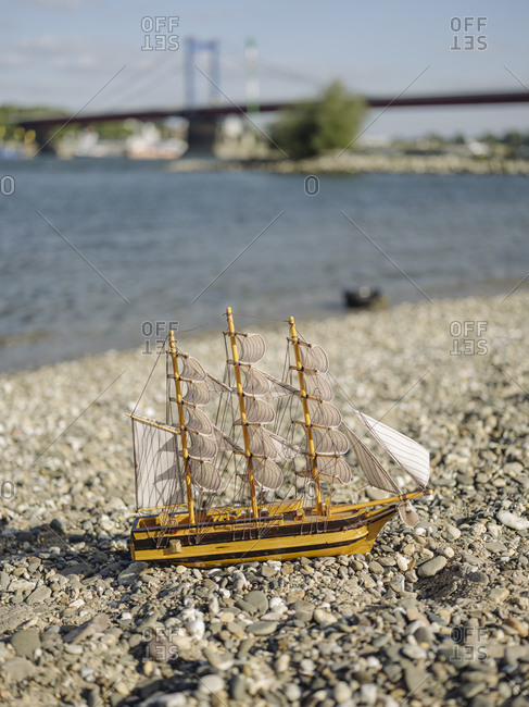 Close-up of toy boat on land against Rhine river
