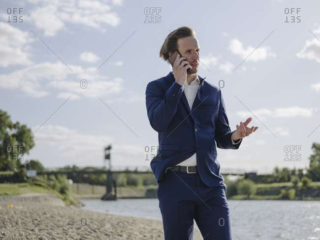 Male entrepreneur talking over smart phone while standing at riverbank against sky