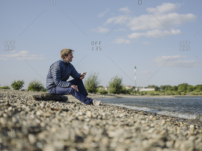 Mature man wearing warm clothing looking at Rhine river while sitting on land against sky