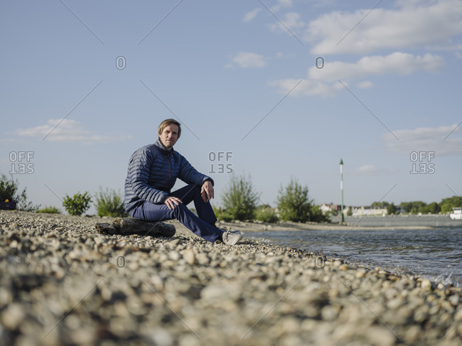 Mature man wearing warm clothing sitting at riverbank against sky on sunny day