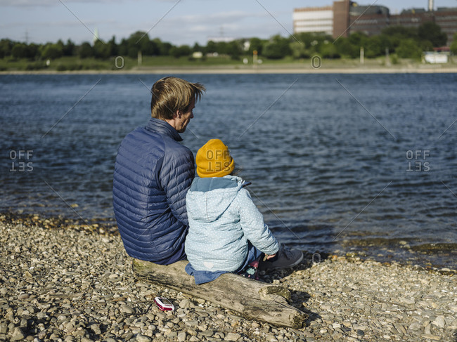 Father and daughter looking at Rhine river while sitting on log during sunny day