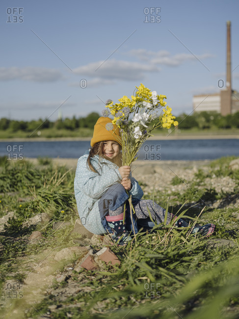 Smiling girl holding flowers while sitting on grassy land against sky