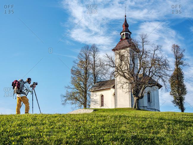 Slovenia- Upper Carniola- Municipality of Skofja Loka- Man photographing Saint Thomass Church in autumn
