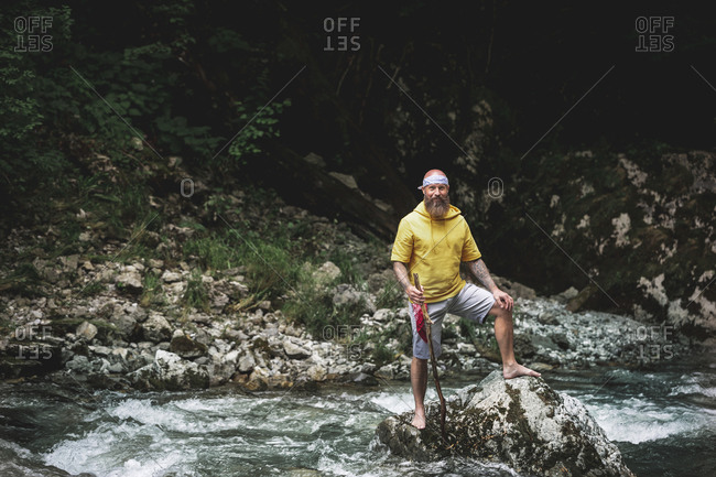 Adventurer with beard sitting in the middle of river on stone and carving on piece of wood