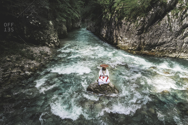 European yamabushi monk sitting on rock in the middle of river and meditating