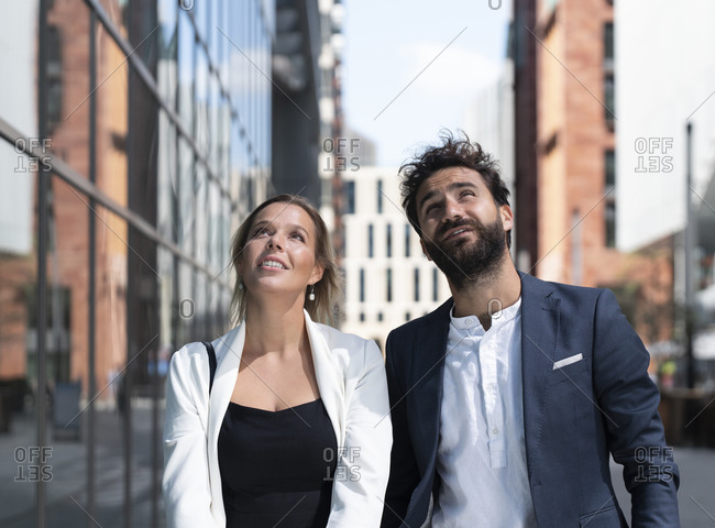 Businessman and businesswoman in business district in the city looking up