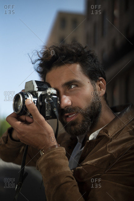 Portrait of man taking picture in the city with old-fashioned camera