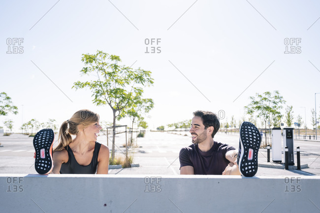 Smiling couple with feet up exercising on retaining wall against clear sky during sunny day