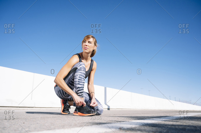Mid adult woman looking away while tying shoelace on road against clear blue sky