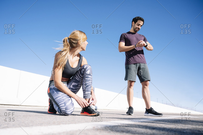 man checking time while woman tying shoelace on road against clear blue sky in city