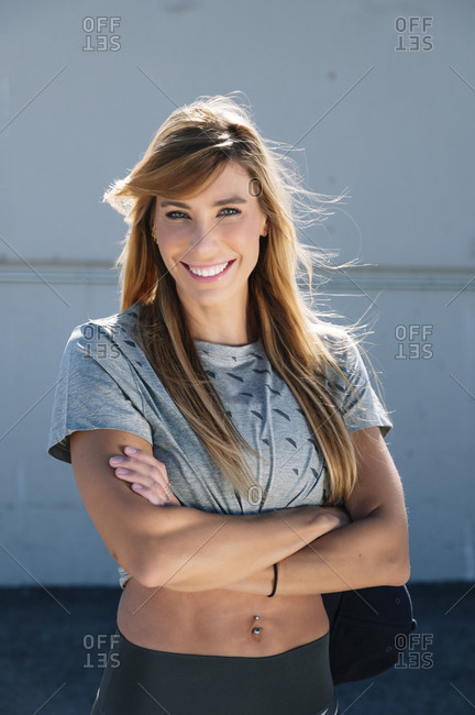 Smiling mid adult woman with arms crossed standing against wall in city