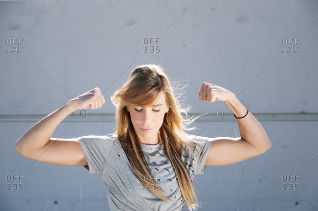 Confident woman flexing muscles while standing against wall in city