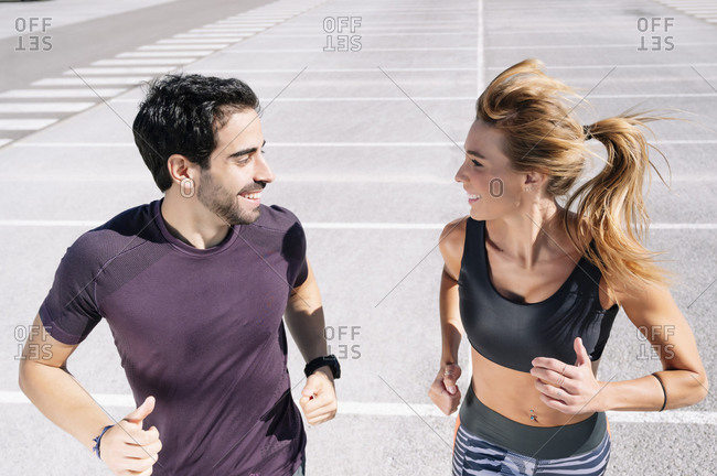 Smiling couple looking at each other while jogging on road in city