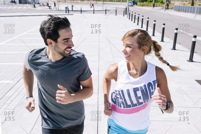 Smiling couple looking at each other while running on sidewalk in city