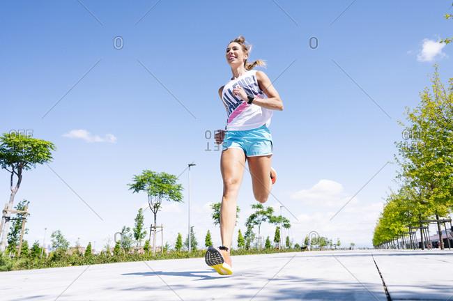 Mid adult woman jogging on street against blue sky