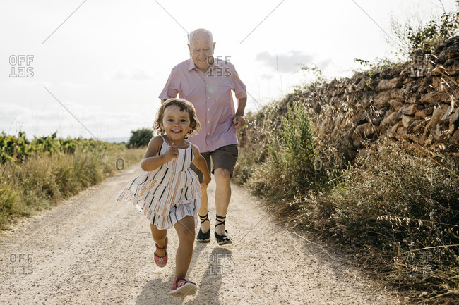 Grandfather running behind playful granddaughter on dirt road against sky
