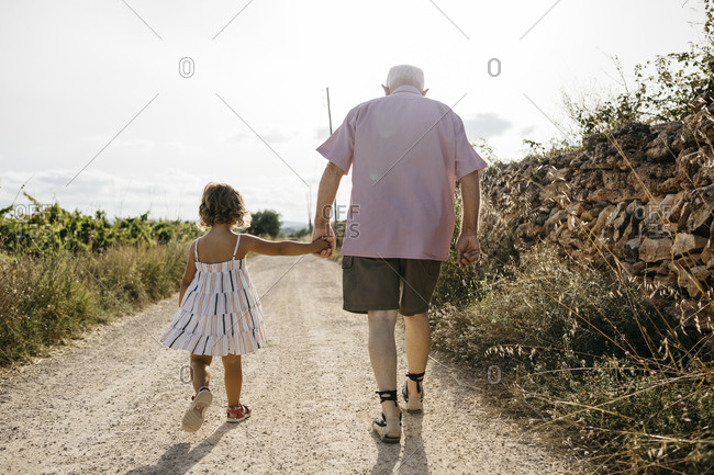 Grandfather holding granddaughter's hand while walking on dirt road against sky